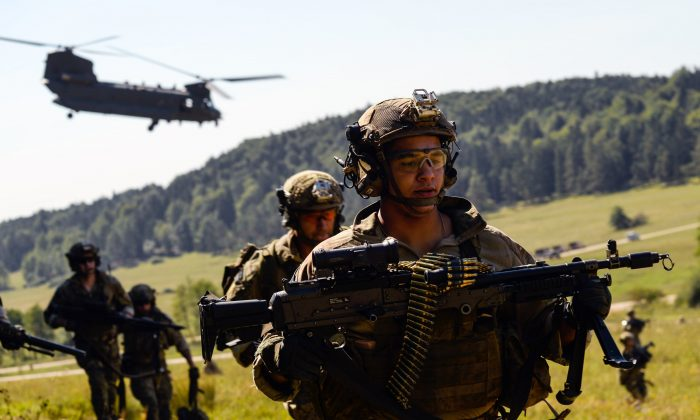 "American special forces soldiers advance as a Chinook helicopter takes off during the ""Swift Response"" airborne training exercise in Hohenfels, southern Germany on Aug. 26, 2015. (Philipp Guelland/AFP/Getty Images)"