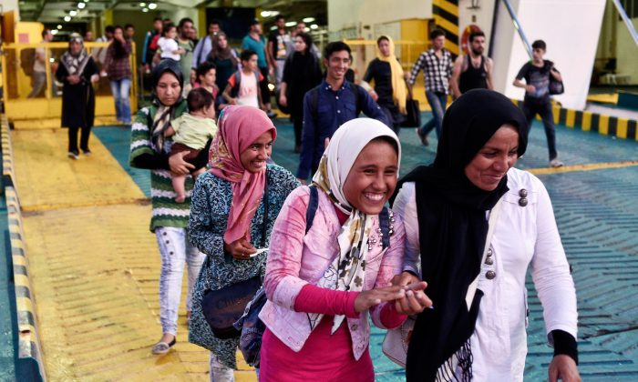 Syrian migrants arrive on a ferry carrying about 2,500 migrants from the Greek islands to the main port of Piraeus on Aug. 26, 2015 in Athens, Greece. (Milos Bicanski/Getty Images)