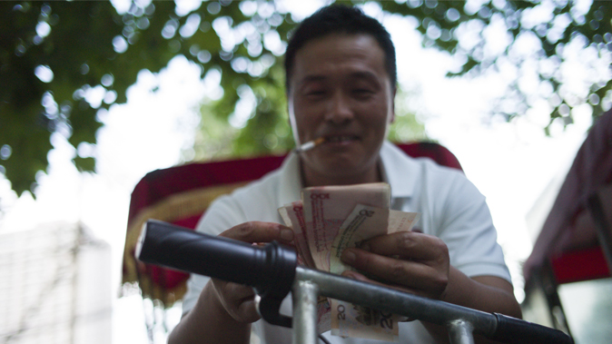 A Chinese man counts his money in Beijing on August 25, 2015. (Fred  Dufour/AFP/Getty Images)