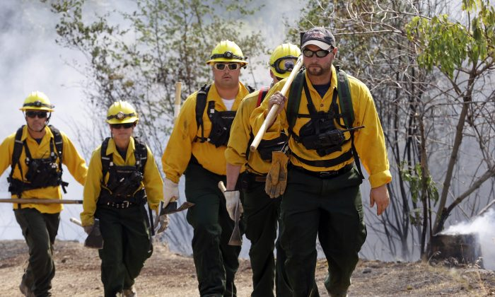 A group of firefighters head up a hill to keep an eye on an area burning between houses and the main fire on Aug. 22, 2015 in Okanogan, Wash. (AP Photo/Elaine Thompson)