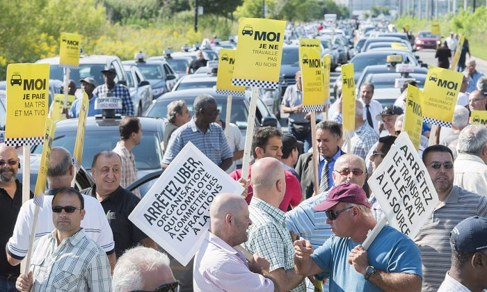 Taxi drivers demonstrate in Montreal after comments made by Quebec Premier Philippe Couillard saying that he'd allow ride-sharing service Uber to operate legally in the province, Aug. 25, 2015. (The Canadian Press/Graham Hughes)