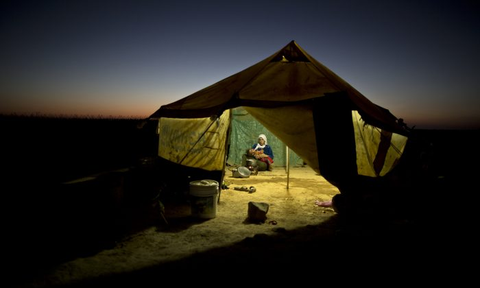 A Syrian refugee woman tends to her daughter while cooking inside her tent at an informal tented settlement near the Syrian border on the outskirts of Mafraq, Jordan, on Aug. 26, 2015. (AP Photo/Muhammed Muheisen)