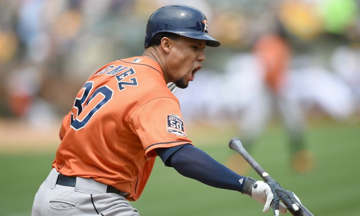 Carlos Gomez of the Houston Astros reacts and tosses his bat after he hits a fly ball for an out to right field against the Oakland Athletics. (Thearon W. Henderson/Getty Images)