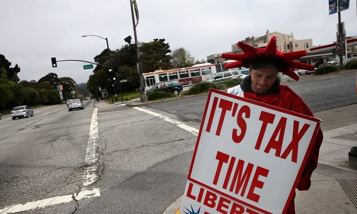 A man holds a sign advertising income tax services for Liberty Tax Service in San Francisco on April 14, 2014. (Justin Sullivan/Getty Images)