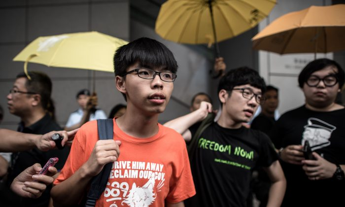 Student protesters Joshua Wong (centre L) and Nathan Law (centre R) stand outside the Wanchai police station in Hong Kong on August 27, 2015. (Philippe Lopez/AFP/Getty Images