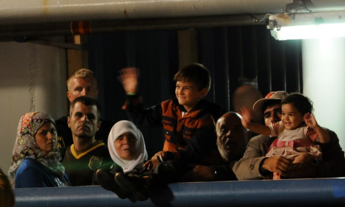 Migrants wait to disembark from Swedish ship Poseidon at the Palermo harbor, Italy, Thursday, Aug. 27, 2015. (AP Photo/Alessandro Fucarini)