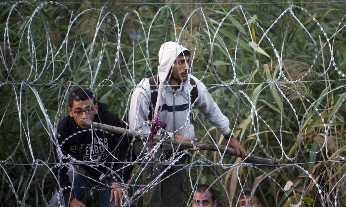 Syrian refugees get ready to enter Hungary from Serbia, on the border near Roszke, Friday, Aug. 28, 2015. Hungary deployed police reinforcements to rein in an unrelenting flow of migrants across its porous border Thursday, but refugee activists said the effort appeared futile in a nation whose migrant camps are overloaded and barely delay their journeys west into the heart of the European Union. (AP Photo/Darko Bandic)