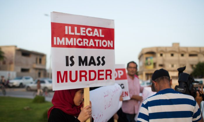 In this Thursday, Aug. 27, 2015 photo, local residents hold a demonstration against illegal immigration after hearing news that a boat carrying hundreds of migrants capsized off the coast, in Zuwara, Libya. (AP Photo/Mohamed Ben Khalifa)