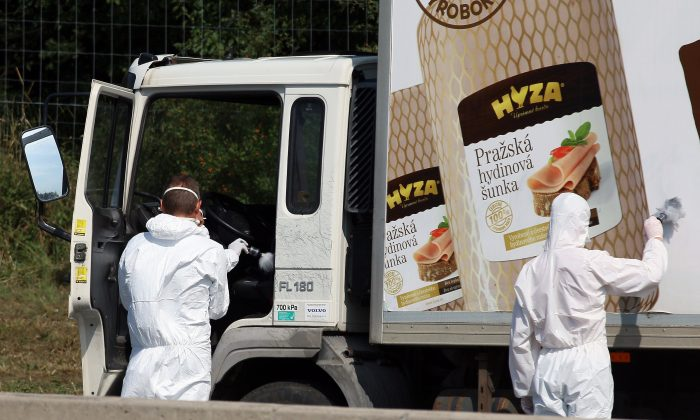 Investigators search  traces at  a  truck that  stands on the shoulder of the highway A4 near Parndorf south of Vienna, Austria, Thursday, Aug 27, 2015. At least 20 migrants were found dead in the truck parked on the Austrian highway leading from the Hungarian border, police said. (AP Photo/Ronald Zak)