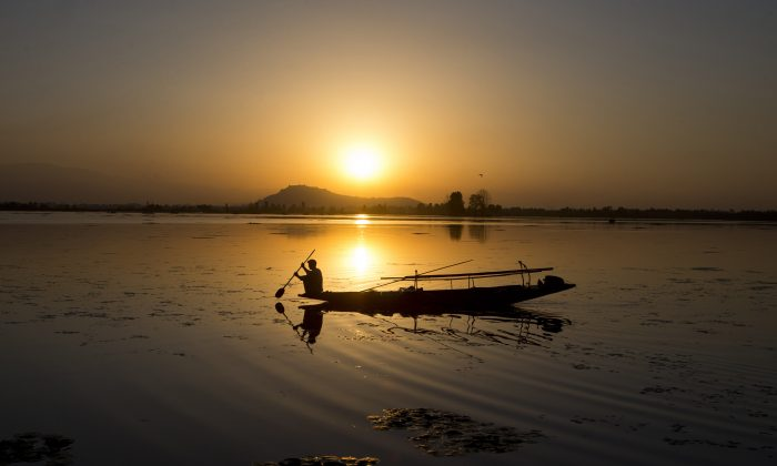 A Kashmiri fisherman rows his Shikara, or traditional boat, during sunset at the Dal Lake in Srinagar, Indian controlled Kashmir, on Aug. 29, 2015. (Dar Yasin/AP Photo)