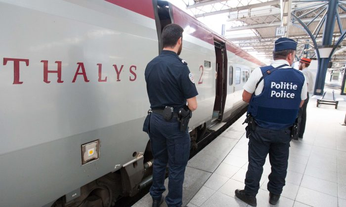 In this Aug.22, 2015 file photo, member of Belgian and French police stay next to a Thalys train at the Brussels Midi - Zuid train station. The attack Aug. 21 on the Thalys train from Amsterdam to Paris happened at the height of the summer travel season. (AP Photo/Francois Walschaerts)