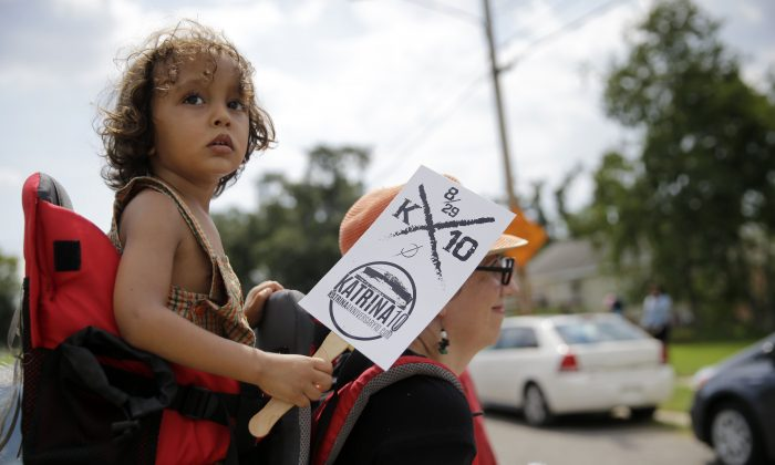 Rizzo Santana, 2, walks with his mother Sierra Santana during a second-line parade to commemorate the 10th anniversary of Hurricane Katrina in the Lower 9th Ward of New Orleans, Saturday, Aug. 29, 2015. (AP Photo/Gerald Herbert)