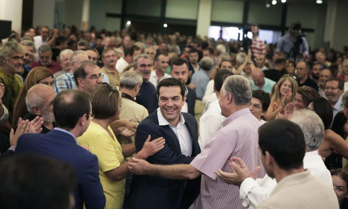Outgoing Greek Prime Minister and the Syriza party leader Alexis Tsipras, center, arrives at a gathering of his party members in Athens, on Saturday, Aug. 29, 2015. (AP Photo/Petros Giannakouris)