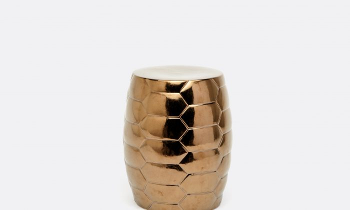 This photo provided by Made Goods shows an oversized tortoise shell motif that sets the stage for a ceramic stool that is finished in crackled gold or black pearl, made in Vietnam. August's NY Now gift and design show included decor with a worldly vibe. (Made Goods via AP)