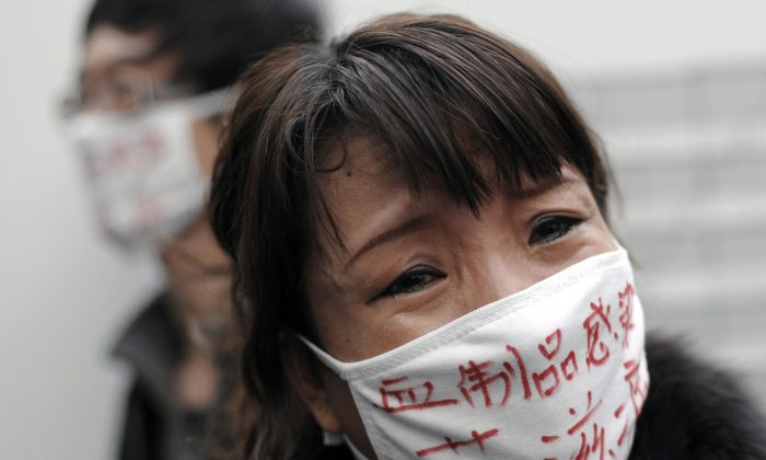 """A woman, whose son was infected with HIV, wears a face mask bearing the words """"Blood products infect us with AIDS,"""" as she cries during an AIDS awareness event on the World AIDS Day held at Beijing's south railway station on Dec. 1, 2009. (Andy Wong/AP Photo)"""