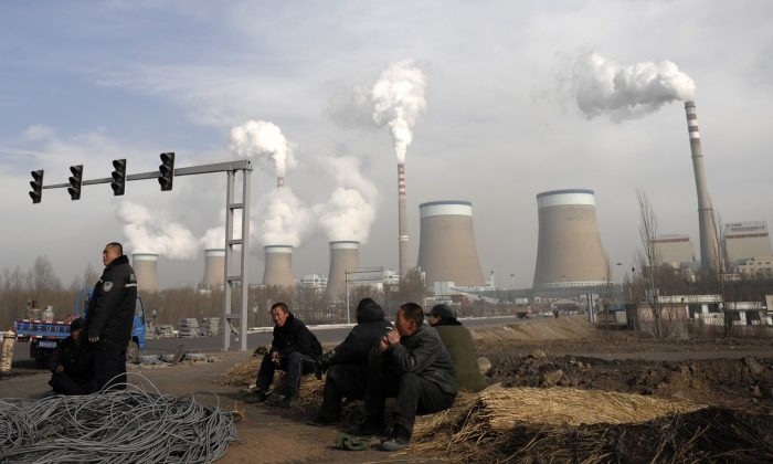 Chinese workers take a break in front of the cooling towers of a coal-fired power plant in Dadong, Shanxi province, China, on Dec. 3, 2009. (AP Photo/Andy Wong, File)