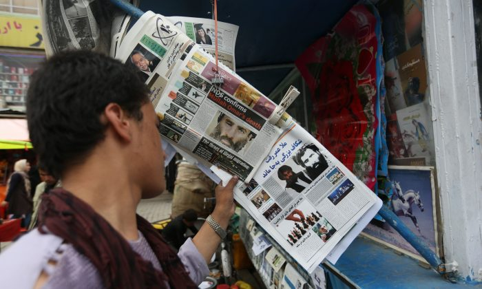 In this Saturday, Aug. 1, 2015, photo, An Afghan boy reads a local newspaper at a news stand carrying a headline about the new leader of the Afghan Taliban, Mullah Akhtar Mohammad Mansoor, in Kabul, Afghanistan.  (AP Photo/Rahmat Gul)
