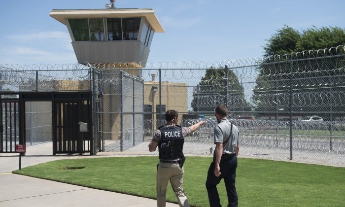Police and a prison guard patrol the entrance of the El Reno Federal Correctional Institution, in El Reno, Okla., on July 16, 2015. (Saul Loeb/AFP/Getty Images)