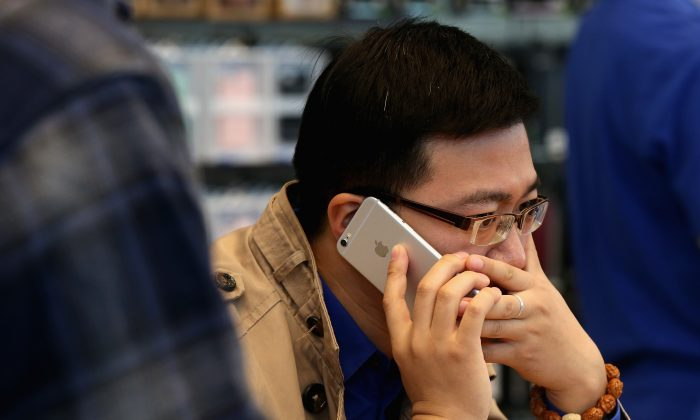 A Chinese man answers the phone with his new iPhone 6 Plus inside an Apple store on October 17, 2014 in Beijing, China. Apple Inc began delivering its popular smartphone iPhone6 and iPhone6 Plus to the Chinese mainland on Friday.  (Feng Li/Getty Images)