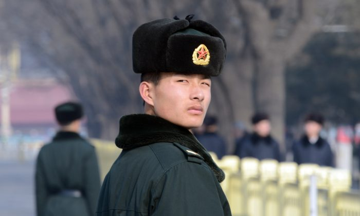 A Chinese paramilitary policeman keeps an eye on visitors to Tiananmen Square in Beijing on Jan. 27, 2014. Authorities recently punished nearly 200 Internet users for expressing themselves online. (Goh Chai Hin/AFP/Getty Images)
