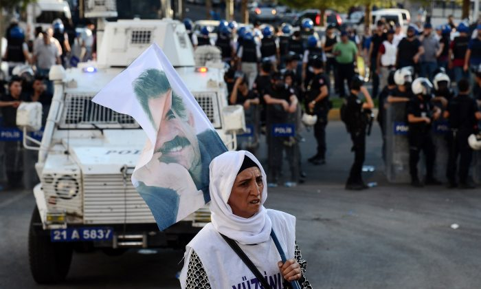 A woman holds a flag of jailed Kurdish leader Abdullah Ocalan as she stands opposite Turkish riot police in Diyarbakir on August 1, 2015 during a demostration against Ocalan's social isolation and restrictions on communication with members of his family and lawyers. (Ilyas Akengin/AFP/Getty Images)