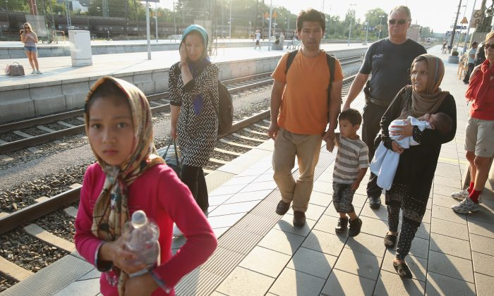 Police escort a family from Afghanistan who were among 190 migrants police detained from a train that arrived from Budapest at Rosenheim railway station on August 31, 2015 in Rosenheim, Germany. (Sean Gallup/Getty Images)