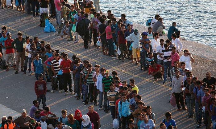 Migrants wait to board a ferry from the island of Kos, Greece, for transport to the Greek mainland port of Piraeus on Monday, Aug. 31, 2015. (Win McNamee/Getty Images)