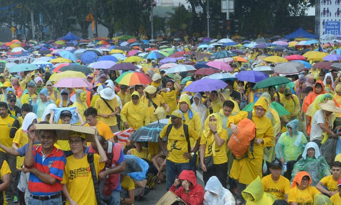 Malaysian protesters gather in the rain during a rally in Kuala Lumpur, Malaysia on Sunday, Aug. 30, 2015. (AP Photo)