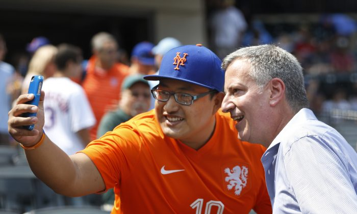 A New York Mets and soccer fan takes a photo with New York Mayor Bill de Blasio, right, before an interleague baseball game between the Mets and the Boston Red Sox in New York, Sunday, Aug. 30, 2015. (AP Photo/Kathy Willens)