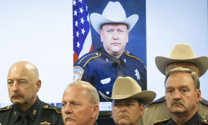 Law enforcement officers attend a news conference regarding the shooting death of Harris County Sheriff's Deputy Darren Goforth, pictured in back, Saturday, Aug. 29, 2015, in Houston. (Marie D. De Jesus/Houston Chronicle via AP)
