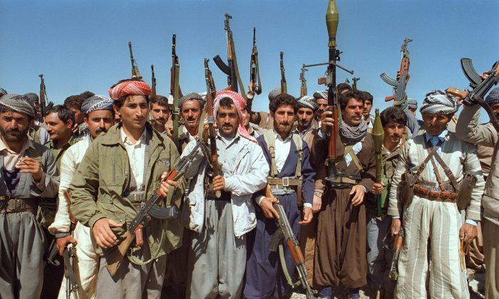 Several Kurdish Peshmerga fighters brandish their arms near Salaheddine, Iraq, on March 27, 1991. (Ramzi Haidar/AFP/Getty Images)