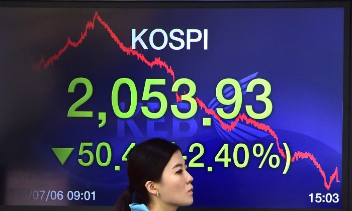 A currency dealer walks past a screen showing South Korea's benchmark stock index in a trading room at the Korea Exchange Bank in Seoul on July 6, 2015.(Jung  Yeon-Je/AFP/Getty Images)