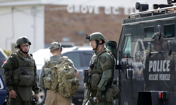 Police officers gather before heading out for a manhunt after an officer was shot in Fox Lake, Ill., on Tuesday, Sept. 1, 2015.  (Stacey Wescott/Chicago Tribune via AP)