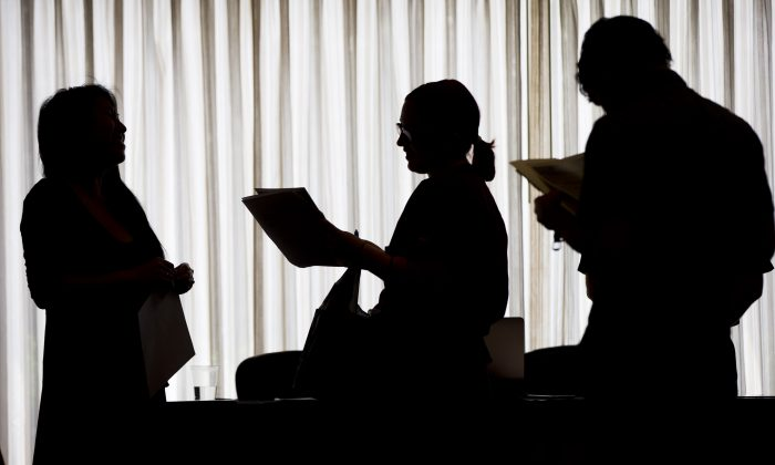 Recruiter Christina O. (L), with New Western Acquisitions, meets with employment seekers during a job fair in Philadelphia, on June 23, 2014. (Matt Rourke/AP)