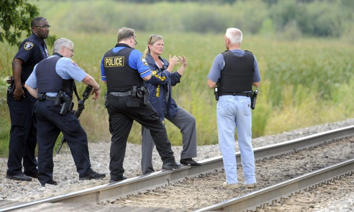 Police officers confer while searching for suspects in the shooting of a police officer Tuesday, Sept. 1, 2015  outside Fox Lake, Ill. (AP Photo/Michael Schmidt)