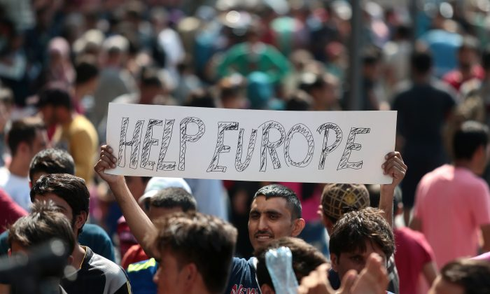 "A man hold a placard reading ""Help Europe"" as Syrian and Afgan refugees attend a protest rally to demand to travel to Germany, outside the Keleti (East) railway station in Budapest, on Sept. 2, 2015. (Ferenc  Isza/AFP/Getty Images)"