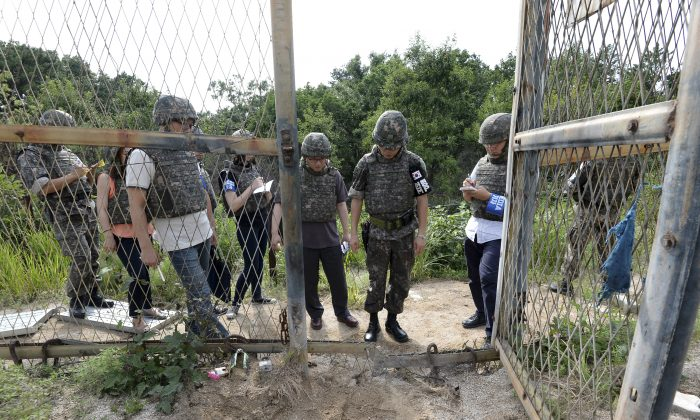 In this Aug. 9, 2015 file photo provided by the Defense Ministry, an unidentified South Korean army official, second from right, gives a briefing to the media at the scene of a blast inside the demilitarized zone in Paju, South Korea. (The Defense Ministry via AP)
