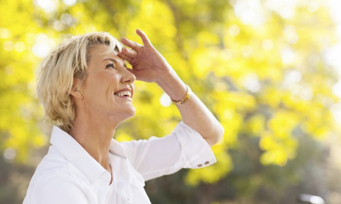 cheerful mature woman looking up outdoors