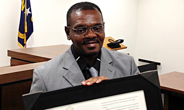 Henry McCollum holds a framed copy of his pardon before a hearing on compensation by the state for his wrongful conviction on Sept. 2, 2015 in Raleigh, N.C. (AP Photo/Jonathan Drew)