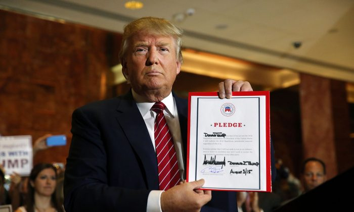 Donald Trump holds up a pledge at a news conference in Manhattan after he signed the pledge Thursday to support the Republican nominee in the 2016 general election, ruling out a third-party or independent run on September 3, 2015 in New York City. Trump made the announcement following a meeting with  Republican National Committee chairman Reince Priebus. Trump stressed repeatedly in the news conference that he is leading in all national polls.  (Photo by Spencer Platt/Getty Images)