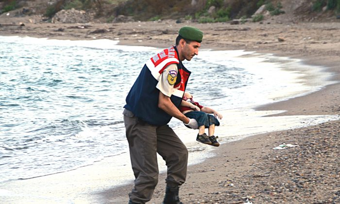 A paramilitary police officer carries the lifeless body of an unidentified migrant child, lifting it from the sea shore, near the Turkish resort of Bodrum, Turkey, early Wednesday, Sept. 2, 2015. (AP Photo/DHA)