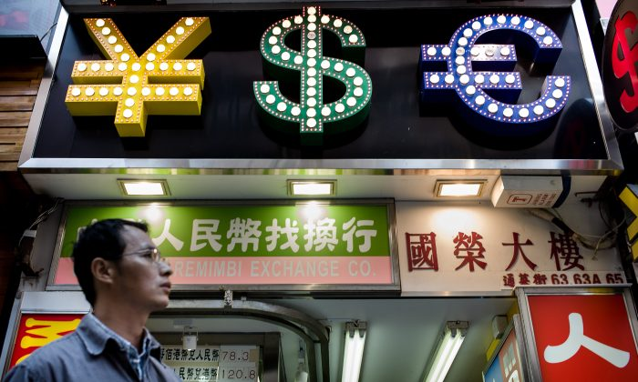 A man walks past a money exchange booth in Hong Kong, October 25, 2013 (PHILIPPE LOPEZ/AFP/Getty Images)