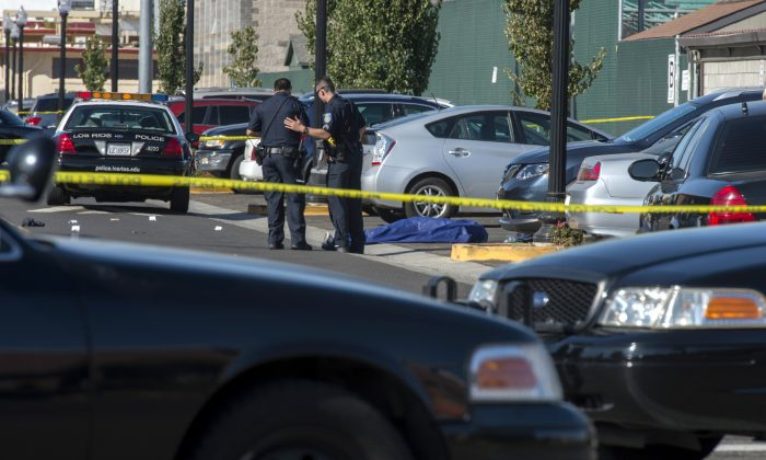 Police officers stand near the body of a victim killed in a shooting at Sacramento City College, Thursday, Sept. 3, 2015, in Sacramento, Calif. The shooting occurred in a parking lot near the baseball field on the college campus. (Renée C. Byer/The Sacramento Bee via AP)