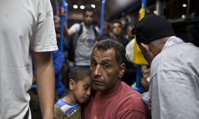 A man and a child ride aboard a bus provided by Hungarian authorities for migrants and refugees at Keleti train station in Budapest, Hungary, Saturday, Sept. 5, 2015. (AP Photo/Marko Drobnjakovic)
