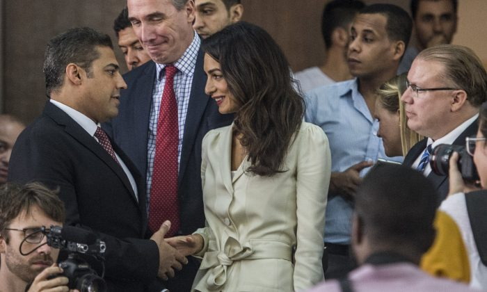 Canadian Al-Jazeera journalist Mohamed Fahmy (L) shakes hands with Amal Clooney (C), the human rights lawyer representing him, before the start of his trial along with Egyptian Baher Mohamed (unseen), both accused of supporting the blacklisted Muslim Brotherhood in their coverage for the Qatari-owned broadcaster, on August 29, 2015, in the capital Cairo. (Khaled Desouki/AFP/Getty Images)