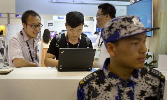 Visitors use a laptop computer at a display booth as a security guard stands nearby at the Global Mobile Internet Conference in Beijing April 29, 2015. (AP Photo/Mark Schiefelbein)