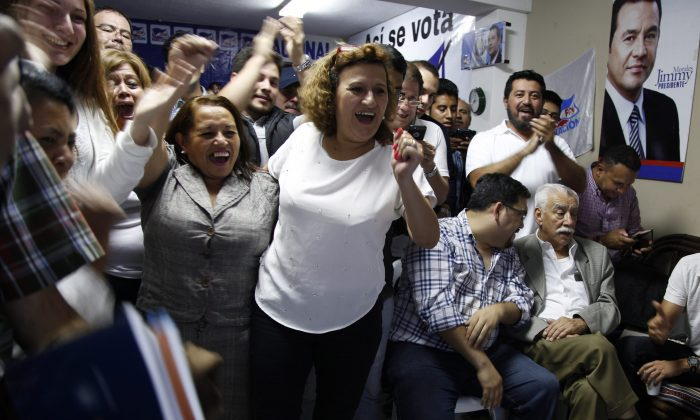 Supporters of television comedian and presidential candidate for the National Front of Convergence party Jimmy Morales, cheer upon listening to the preliminary results of the general elections at their party headquarters in Guatemala City, Sunday, Sept. 6, 2015. (AP Photo/Luis Soto)