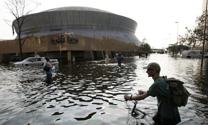 FILE - This Aug, 31, 2005 file photo shows a man pushing his bicycle through flood waters near the Superdome in New Orleans after Hurricane Katrina left much of the city under water. (AP Photo/Eric Gay, File)