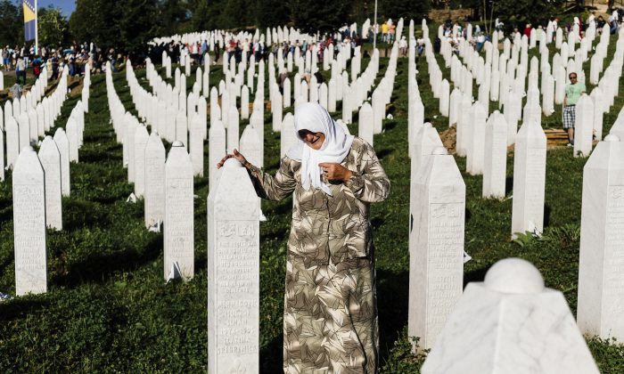 A Bosnian woman mourns at the grave of a relative on July 11, 2015, at the Potocari Memorial Center near the Bosnian Town of Srebrenica, where 136 bodies found in mass grave sites in eastern Bosnia were properly reburied on the 20th anniversary of the Srebrenica Massacre. (Dimitar Dilkoff/AFP/Getty Images)