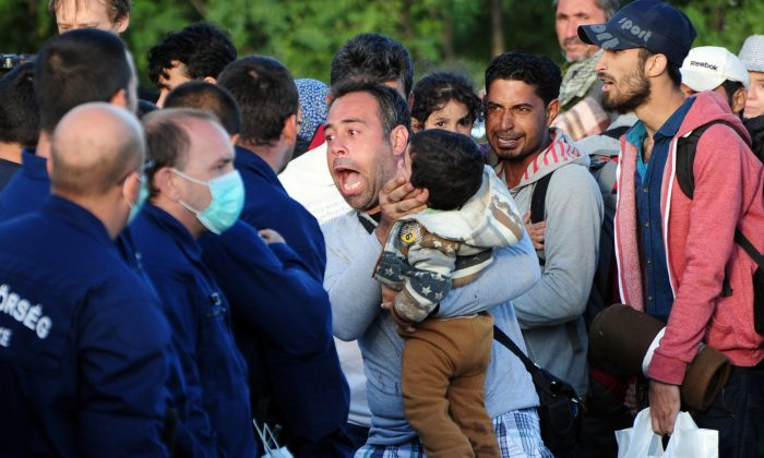 Migrants are stopped by police after the group broke out from a collection point near Roszke village at the Hungarian-Serbian border on September 7, 2015.  (CSABA SEGESVARI/AFP/Getty Images)